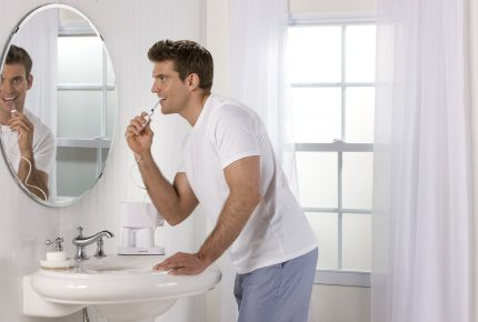 men in bathroom using waterpik