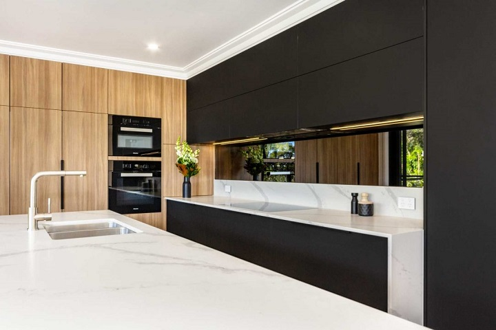 picture of a modern kitchen with black and wooden elements, marble countertop and stainless steel sink and tap ware