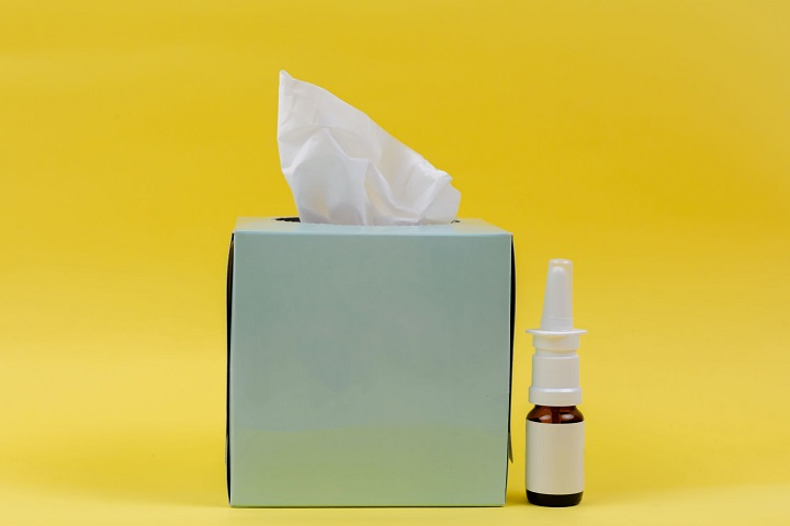 picture of a tissue and a hayfever spray on a yellow background