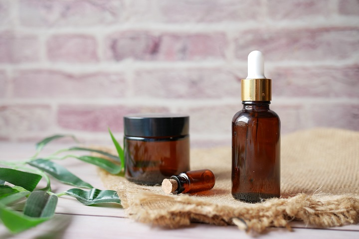 picture of an essential oils in a glass bottle with green leaf on wall background